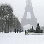A cyclist pedals his bicycle in a garden near the Eiffel Tower as winter weather hits Paris